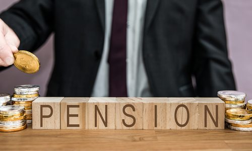 A pensions concept of a businessman saving for or contributing to his pension fund by adding money from his salary, savings, wages and income