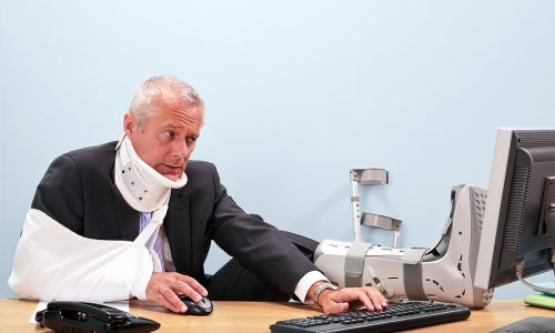 Photo of a mature businessman with multiple injuries sitting at his desk struggling to work on his computer. Good image for health and safety, accident at work or healthcare insurance related themes.
